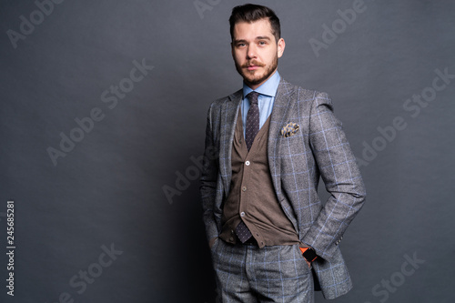 Fotografia  A confident elegant handsome young man standing in front of a grey background in a studio wearing a nice suit