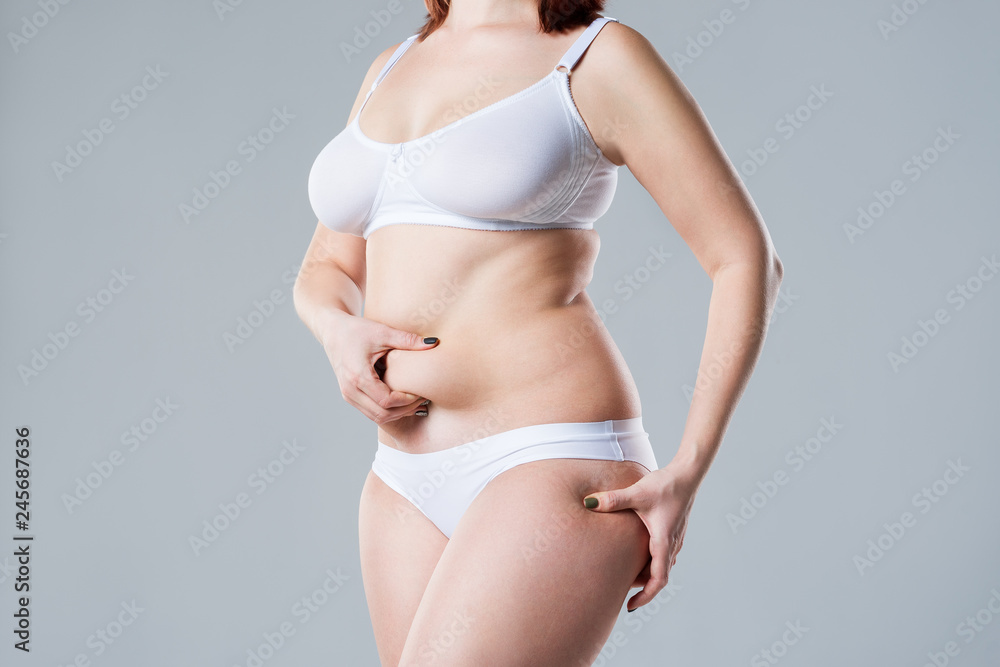 Fototapeta Woman with fat abdomen, overweight female body on gray background