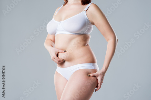 Fotografija  Woman with fat abdomen, overweight female body on gray background