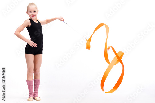 Beautiful teen girl doing rhythmic gymnastics exercises. White background. Holding a ribbon