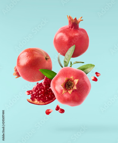 Flying in air fresh ripe pomegranate with seeds and leaves on blue background