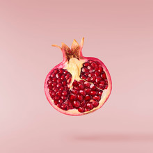 Flying In Air Fresh Ripe Pomegranate Isolated On Yellow Background.