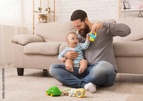 Happy father playing with his baby son with bright rattle Wallpaper Mural