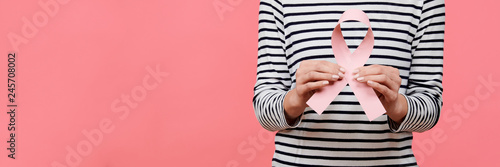 Fotografía  Midsection of a young woman holding pink breast cancer awareness ribbon isolated over living coral background