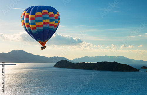 Colorful hot air balloon fly over the blue sea.