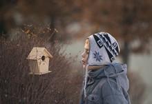 Boy Whistling Beside Bird House