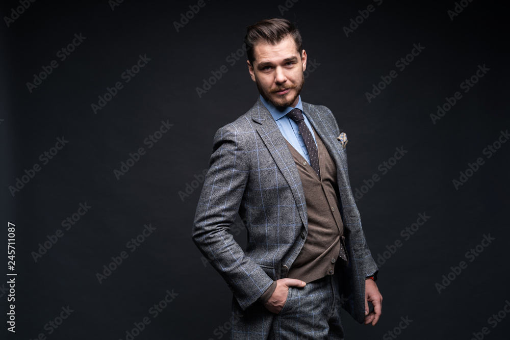 Fototapeta A confident elegant handsome young man standing in front of a black background in a studio wearing a nice suit.