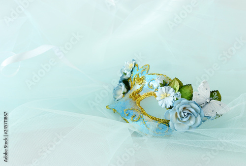 Photo of elegant and delicate blue venetian mask with floral decorations over mint chiffon background.