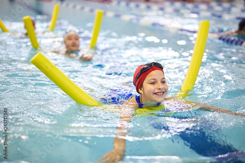 Little girl swimming with noodle in indoor pool and enjoying the process during swimming lesson