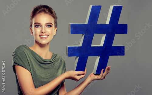 Smiling young woman holding hashtag sign in studio . social media concept