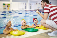 Group Of Little Girls Listening To Recommendation Of The Trainer Before Lesson In The Swimming Pool