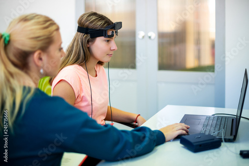 Fotografie, Obraz  Young teenage girl and child therapist during EEG neurofeedback session