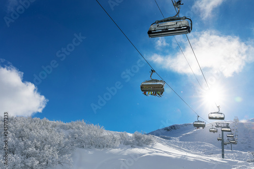 skiers in a ski lift in snowy mountains against blue sunny sky