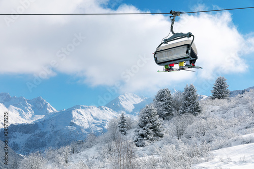 skiers in chairlift above beautiful snowy winter landscape in french Alps