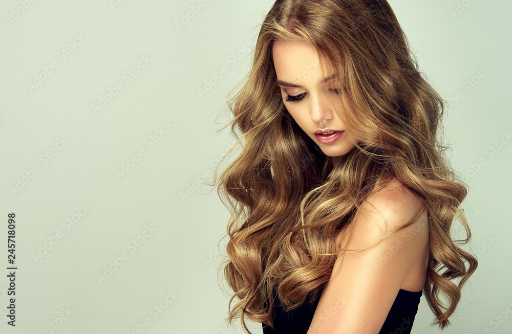 Fototapeta  blonde girl with long  and   shiny wavy hair .  Beautiful  smiling woman model with curly hairstyle .