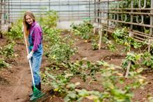 Attarctive Cheerful Girl Raking Leaves In The Garden. Full Length Photo. Plants Care. Hobby. Interest