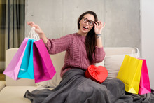Portrait Of A Happy Young Brunette Girl With Glasses Holding Colorful Shopping Bags And A Heart-shaped Present Box On The Couch