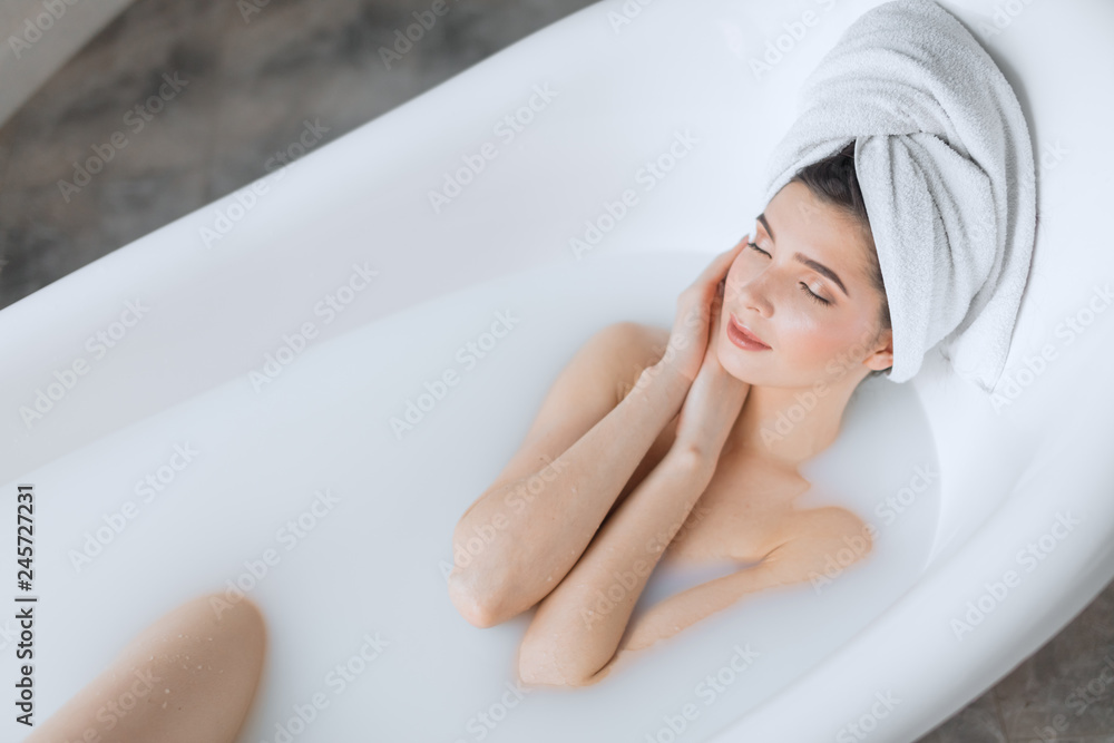 Fototapeta Head and shoulder portrait of beautiful brunette woman in nude make up wearing towel on head while taking homemade relaxing bath at home
