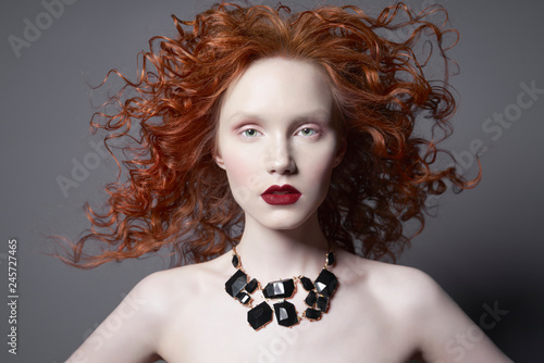 Spoed Foto op Canvas womenART Beautiful young woman with black jewelry and red-hair on grey background. Nude pretty lady with bright red lipsstick and modern art makeup. Sensual model pose in photo-studio. Sexy naked body.