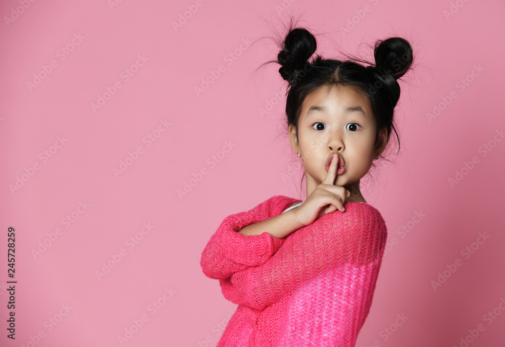 Fototapety, obrazy: Asian kid girl in pink sweater shows shh sign Close up portrait