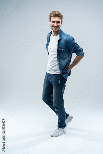 Modern and casual. Full length of handsome young man looking at camera with smile whilestanding against grey background. Wall mural