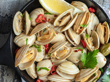 Cooked Seafood Clams In The Iron Pan Portion With Lemon And Seasoning. Close-up