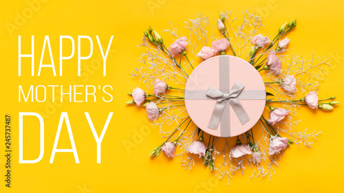 Happy Mother's Day Background. Bright Yellow and Pastel Pink Colored Mother Day Background. Flat lay greeting card with beautiful gift box and pink lisianthus flowers.