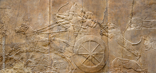 Fotografia Assyrian relief of lions and warriors, ancient art of Mesopotamia
