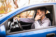 Portrait of young handsome man driving car and speaking on mobile phone.