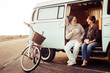 canvas print picture Adult aged caucasian happy couple sit down out of a vintage van drinking a tea and enjoying the outdoor leisure activity during travel vacation - bike parked near the vehicle
