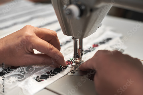 1654cc999a28e Woman seamstress hands connecting white fabric details with floral colorful  embroidery with stripes of lace on modern compact electrical sewing machine.
