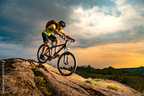 Fotografija Cyclist Riding the Mountain Bike on Rocky Trail at Sunset