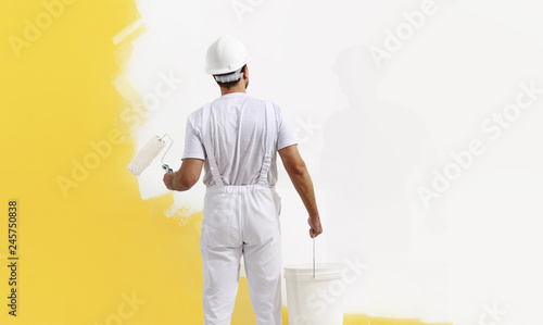 Rear view of painter man painting the wall, with paint roller and bucket, isolated on big empty copy space template