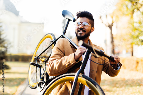 Obraz na plátne Bearded indian hipster man carrying bicycle on shoulder in the city