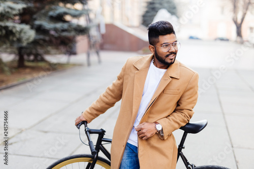 Portrait of indian hipster bearded man in coat walking with fix bicycle on stree Tableau sur Toile