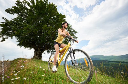 Young Happy Woman Cyclist Riding On Yellow Mountain Bicycle