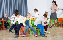 Pupils With Teacher Playing Musical Chairs