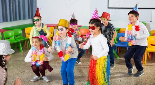 School kids with teacher in festive hats having fun Slika na platnu