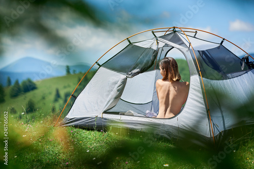 Poster Camping Back view of beautiful naked woman traveller sitting in tent, enjoying sunny day in the mountains. Camping lifestyle concept