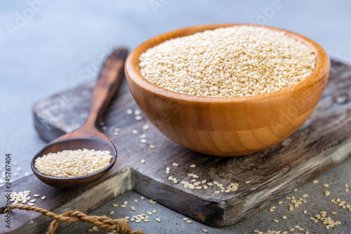 Obraz White sesame seeds in a wooden bowl and spoon. - fototapety do salonu