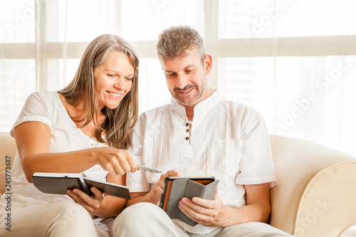 Photographie  Mature couple on a couch with tablet