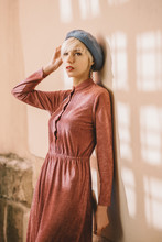 Outdoor Portrait Of Young Beautiful Fashionable Woman Wearing Stylish Pink Dress, Light Blue Beret, Posing In Street. Female Spring Fashion Concept
