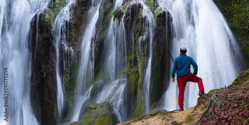 Single man standing near waterfall  - Buy this stock photo