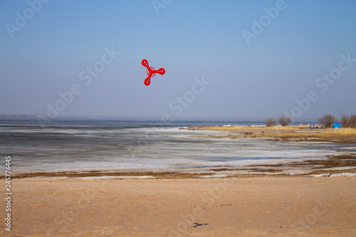 Платно toy red boomerang flying on blue sky background