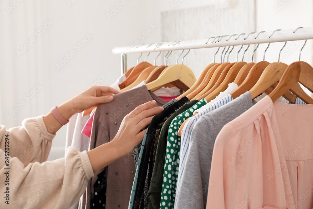 Fototapeta Woman choosing clothes from wardrobe rack, closeup
