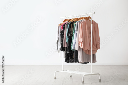 Wardrobe rack with stylish clothes near white wall indoors. Space for text