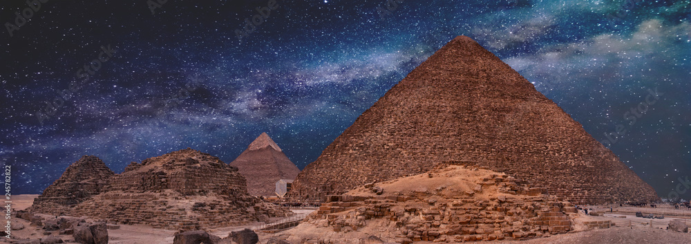 Fototapeta Night sky of the Milky Way over the great pyramids on the plateau of Giza, Egypt, Africa.