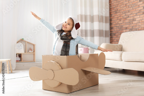 Fotografia Cute little girl playing with cardboard airplane in living room