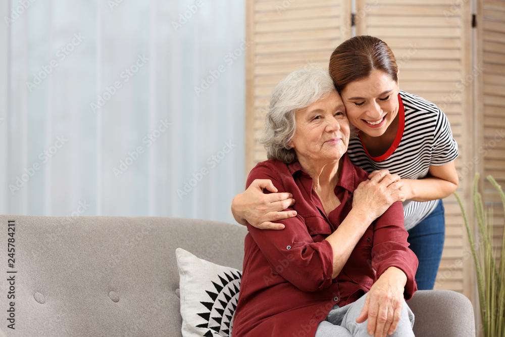 Fototapety, obrazy: Elderly woman with female caregiver in living room. Space for text