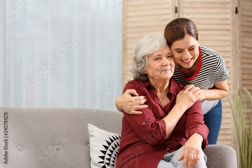 Elderly woman with female caregiver in living room Canvas Print